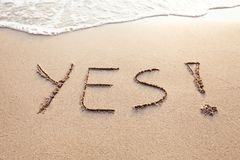 YES concept, positive changes in the life. Word written on sand beach royalty free stock image