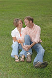 Yes, Dear. A couplen flirt with each other on a carpet of grass Royalty Free Stock Images