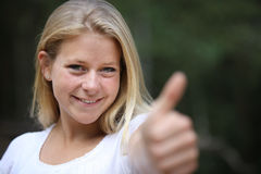 Yes, we did it. Y young woman pointing her thumb towards the camera Royalty Free Stock Photo