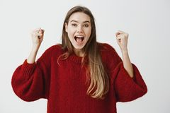 Yes, we did it. Portrait of happy attractive caucasian woman celebrating victory, jumping and raising clenched fists. From positive emotions and happiness Stock Images