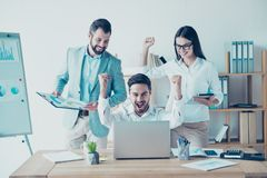 Yes! We did it! Success and team work concept. Team of three bus. Iness partners with raised up hands with fists in light modern work station, celebrating the Royalty Free Stock Images