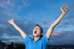Yes - we did it !!!. Teenage boy, standing outside, its evening, screaming, celebrating, throwing his arms up in the air Stock Photos