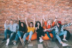 Yes excited millennials hands up support approval. Yes. Group of excited millennials sitting on bean bags. Hands up. Support and approval gesture. Leisure at stock image