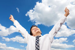 Yes finally. Boy in white shirt is throwing happily his arms high up in the air. He is outside, with background a beautiful blue sky and white clouds Stock Image