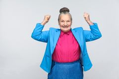 Yes! Happiness success woman rejoicing win. Emotion and feelings, expressive grandmother with light blue suit and pink shirt standing with collected bun gray stock photography