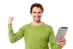 Yes, I did it. I won the game. Young excited man with touch pad device Stock Image