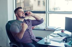 Yes! I did it! Portrait of happy successful businessman in office with smartphone. Good news. Victory. stock image