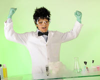 Yes!  I Did It!. A preteen mad scientist displaying vicotory as fluid in his beaker vaporizes Stock Image