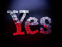 Yes means No. Word yes written of multiple noes on black background illuminated with white and red light Royalty Free Stock Image