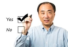 Yes or no. Asian man checks YES on yes or no check list Stock Photography
