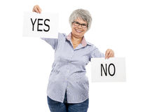 Yes or No choice. Happy elderly woman holding a paper card and choosing between Yes or No choice Royalty Free Stock Photography