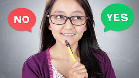 Yes or No. Close up face of happy Asian woman in consideration between YES or NO answer, over grey background Stock Image