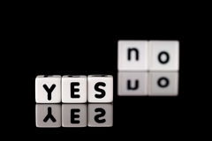 Yes No Concept. Yes spelled in dice letters in foreground with the word no out of focus in background. Isolated on black background Stock Images