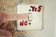 Yes Or No. Human hand close to electric switch with a hand written Yes and No. Concept of taking a decision Royalty Free Stock Photos