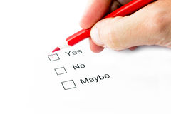 Yes or no or maybe choice. A hand doing selection with a red pencil Royalty Free Stock Photography