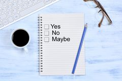 Yes No Maybe on notebook. On a wooden table Royalty Free Stock Image
