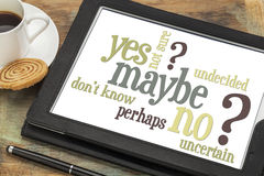 Yes, no, maybe word cloud. Undecided or uncertain concept - yes, no, maybe  word cloud on a digital tablet with a cup of coffee Royalty Free Stock Image