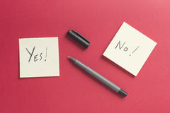 Yes no paper notes post on a red background Stock Images