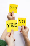 YES NO. People holding YES and NO adhesive notes up Royalty Free Stock Image