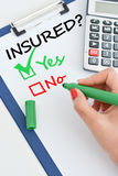 Yes or no question regarding the insurance. Yes or no question about the insurance with calculator and green pen Royalty Free Stock Photo