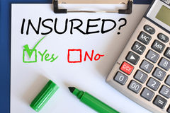 Yes or no question regarding the insurance. Yes or no question about the insurance with calculator and green pen Stock Photos