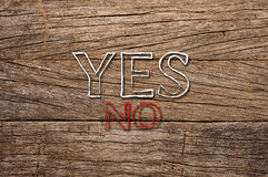 Yes and No in red written over wooden background Royalty Free Stock Images