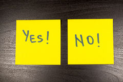 Yes and no sticky note on wooden background Royalty Free Stock Photos