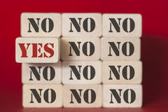 Yes and No words on wooden blocks. YES word standing out from the NO words. Positivity, acceptance and standing out from the crowd concept with wooden tiles on Royalty Free Stock Photos