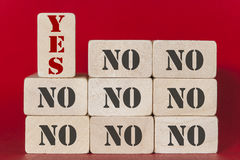 Yes and No words on wooden blocks. YES word standing out from the NO words. Positivity, acceptance and standing out from the crowd concept with wooden tiles on Royalty Free Stock Image