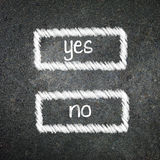 Yes or no written on the blackboard with white chalk. Your choic Stock Photos