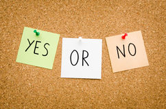 Yes or no. Written on red white and green post notes pinned to a board suggesting options to accept or deny in a bussines look in landscape mode Royalty Free Stock Photo