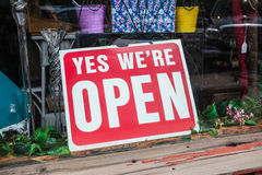Yes We're Open Sign. Red and white sign in store window saying Yes We're Open Royalty Free Stock Photography
