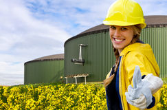 Yes to biogas !. Young woman in workwear with thumb up, in background rape field and gas storage Stock Image