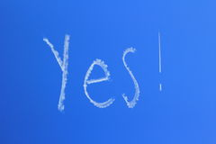 Yes skywriting in clear blue sky Stock Photo