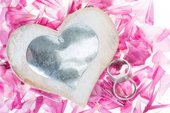 Yes. White heart and two rings with metallic lying on magenta petals Stock Images