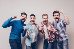 Yes! Winners! Four cheerful young men are standing and gesturing. For the victory on pure background in casual outfit and jeans. They are fans of sports games Royalty Free Stock Photos