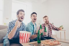 Yes! Winners! Goal! Cheerful young guys are watching match on co. Uch at home and drink beer, eat pizza and pop corn from box. They are fans of sports games as stock photo