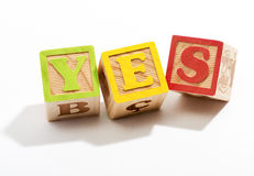 Yes in Wooden Letter Blocks on White Background Royalty Free Stock Photography