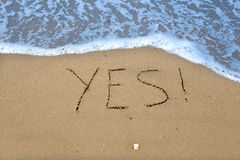 Yes. Written in the sand at the beach Royalty Free Stock Photo