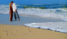 Yes Written in Sand by couple Stock Images