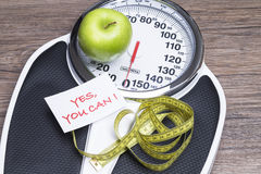 Yes you can. Concept photography for healthy life with apple, bathroom scales and tape measure royalty free stock photography