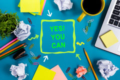 Yes you can. Office table desk with supplies, white blank note pad, cup, pen, pc, crumpled paper, flower on blue Stock Photos