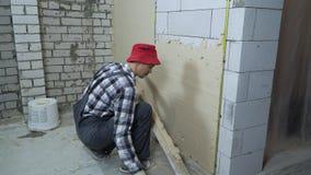Yeso de extensión del constructor en la pared aireada del bloque de cemento con la regla de la construcción almacen de video