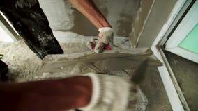 Yeso del mortero de la pared del oshtukaturivayut del empleado El constructor aplica una solución del yeso en la espátula almacen de video