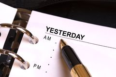 Yesterday. Open day planner with a gold fountain pen pointing to YESTERDAY Royalty Free Stock Image