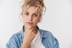 Yeux bleus aux cheveux bouclés focalisés attrayants curieux de femme de Scandinave blond millénaire élégant frottant le regard de images stock