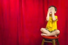 Yeux de bâche de garçon se reposant sur des selles devant le rideau rouge photographie stock