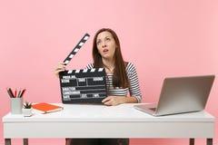 Yeux de roulement épuisés de femme tenant la claquette noire classique de cinéma et travaillant sur le moment de projet pour se r image stock
