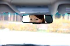 Yeux femelles dans le salon un miroir de véhicule Photographie stock libre de droits