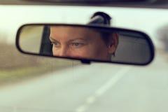 Yeux femelles se concentrant sur la route, réflexion dans la MIR de rearview de véhicule Images stock